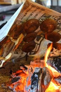 囲炉裏で新聞紙を掛けて焼きます